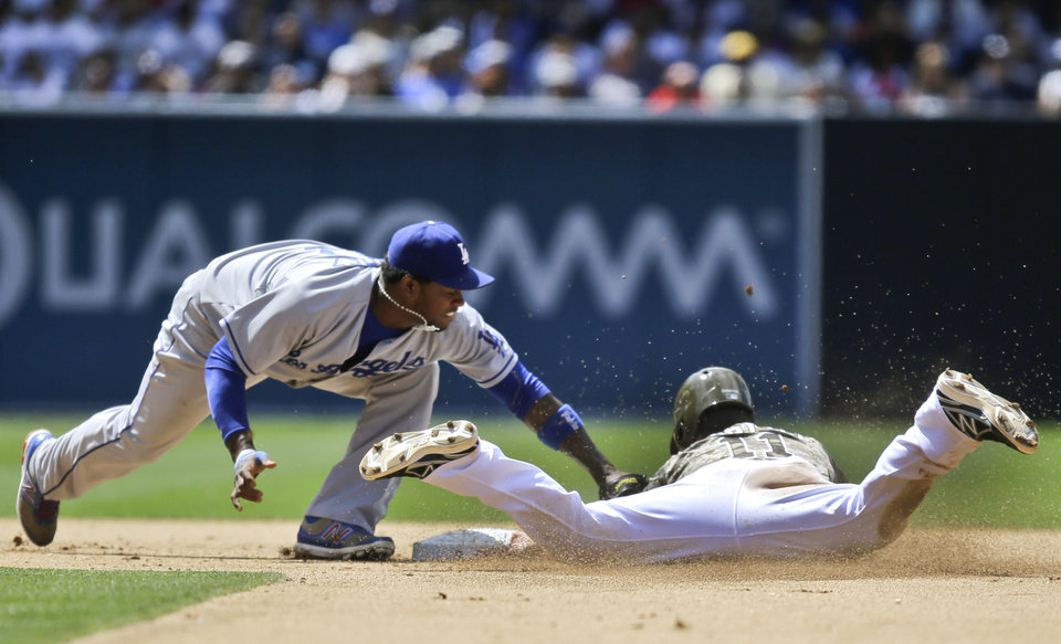 Photo - San Diego Padres' Logan Forsythe is tagged out by Los Angeles Dodgers shortstop Hanley Ramirez,left, while trying to steal second in the sixth inning of a baseball game in San Diego, Sunday, June 23, 2013. (AP Photo/Lenny Ignelzi)