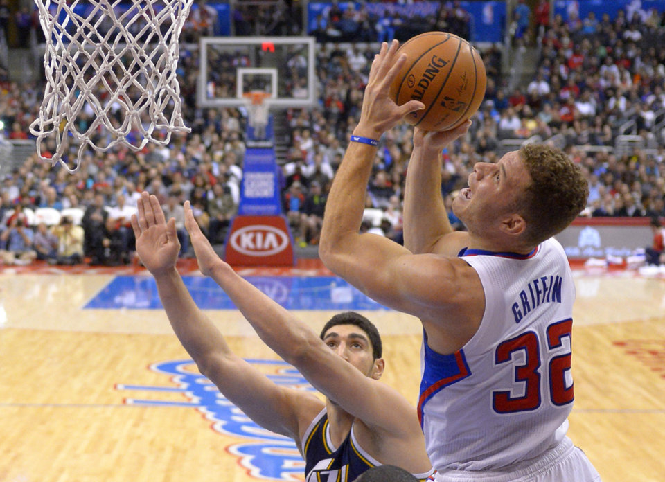 Photo - Los Angeles Clippers forward Blake Griffin, right, puts up a shot as Utah Jazz center Enes Kanter defends during the first half of an NBA basketball game, Saturday, Feb. 1, 2014, in Los Angeles. (AP Photo/Mark J. Terrill)