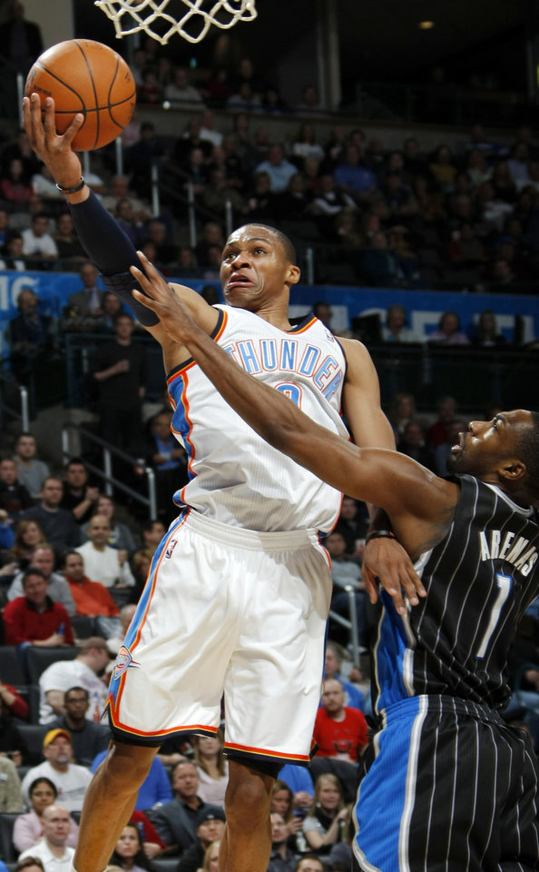 Photo - Oklahoma City's Russell Westbrook (0) takes a shot past Gilbert Arenas (1) of Orlando during the NBA basketball game between the Orlando Magic and Oklahoma City Thunder in Oklahoma City, Thursday, January 13, 2011. Oklahoma City won, 125-124. Photo by Nate Billings, The Oklahoman