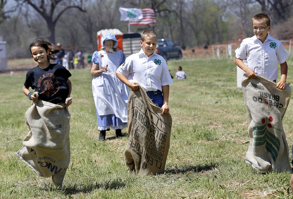 Photo -  Bailey Barrett, 10, of Wellston, left, crosses the finish line for first place in a sack race. Cheering in the background is Joyce Stockton. Stockton is with women from Grady County Rural Neighbors, an Oklahoma Home and Community Education Group in Chickasha, which hosted a tent where children could play games typical of ones played by young people in the early 1900s. The Oklahoma Cooperative Extension Service celebrated tits 100th anniversary with a Whistle-Stop and Festival on Saturday in Wellston. Photo by Jim Beckel, The Oklahoman   Jim Beckel -