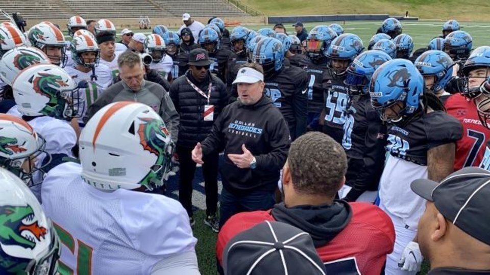 Photo -  Dallas Renegades coach Bob Stoops, wearing visor, and Seattle Dragons coach Jim Zorn address their teams after a recent two-way practice. [Photo provided]