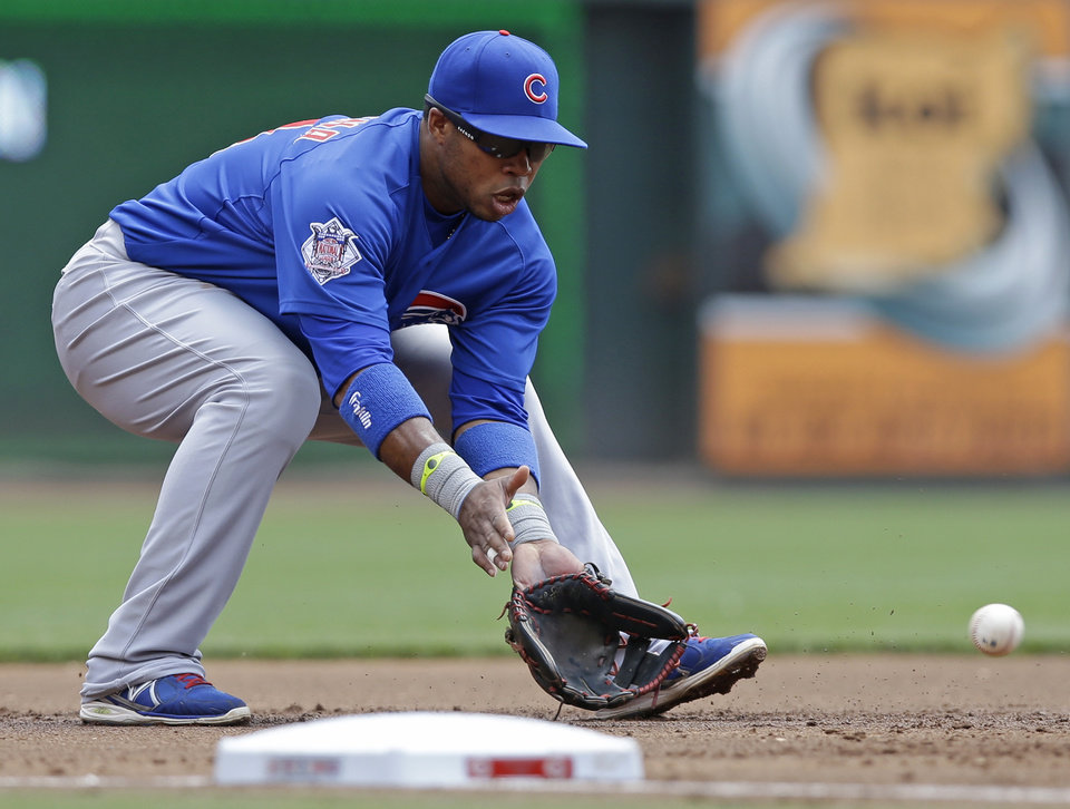 Photo - Chicago Cubs third baseman Luis Valbuena fields a ground ball hit by Cincinnati Reds' Devin Mesoraco in the first inning of a baseball game, Tuesday, July 8, 2014, in Cincinnati. Valbuena threw Mesoraco out at first. (AP Photo/Al Behrman)
