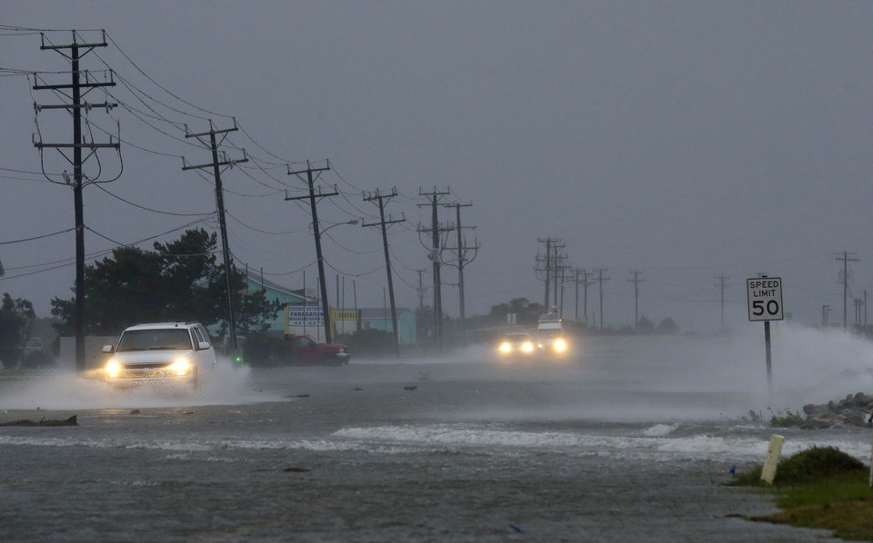 Photo - Vehicles navigate a flooded Highway 64 as wind pushes water over the road as Hurricane Arthur passes through Nags Head, N.C., Friday, July 4, 2014. (AP Photo/Gerry Broome)