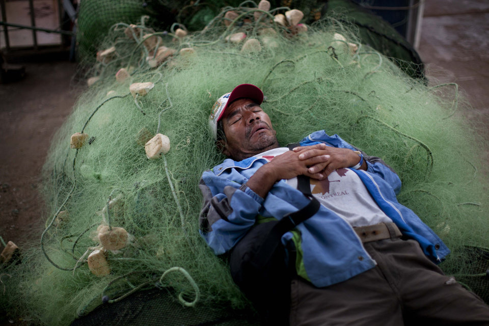 Photo - A small scale fisherman naps on a jumble of fishing nets in Lima, Peru, Wednesday, April 2, 2014. Chilean authorities discovered surprisingly light damage Wednesday from a magnitude-8.2 quake that struck in the Pacific Ocean, Tuesday evening, near the mining port of Iquique, about 87 miles from the Peruvian border. Tsunami warnings issued for Chile, Peru and Ecuador have been lifted. Six deaths have been reported. (AP Photo/Rodrigo Abd)