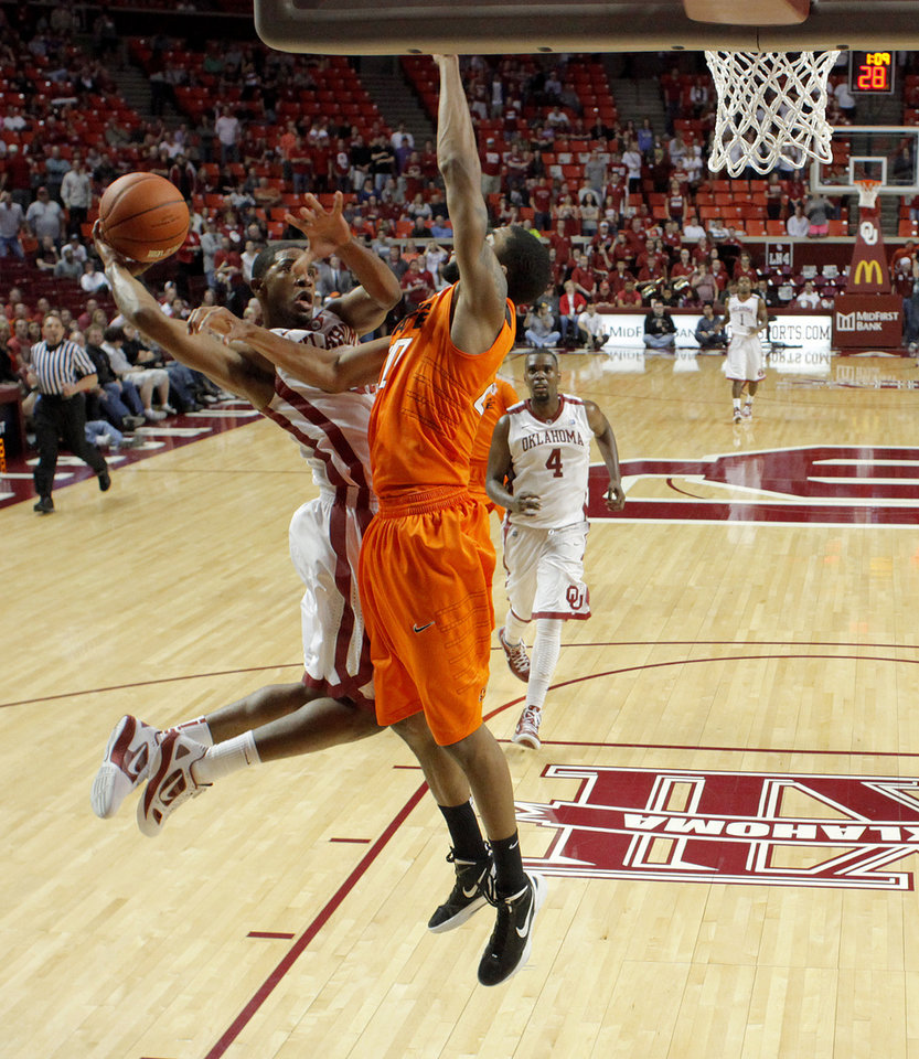 Photo - Oklahoma's Cameron Clark (21) goes to the basket beside Oklahoma State's Michael Cobbins (20) during the Bedlam men's college basketball game between the University of Oklahoma Sooners and the Oklahoma State Cowboys in Norman, Okla., Wednesday, Feb. 22, 2012. Oklahoma won 77-64. Photo by Bryan Terry, The Oklahoman