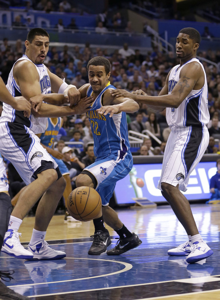 New Orleans Hornets' Brian Roberts (22) goes after a loose ball between Orlando Magic's Gustavo Ayon, left, of Mexico, and E'Twaun Moore, right, during the first half of an NBA basketball game on Wednesday, Dec. 26, 2012, in Orlando, Fla. (AP Photo/John Raoux)
