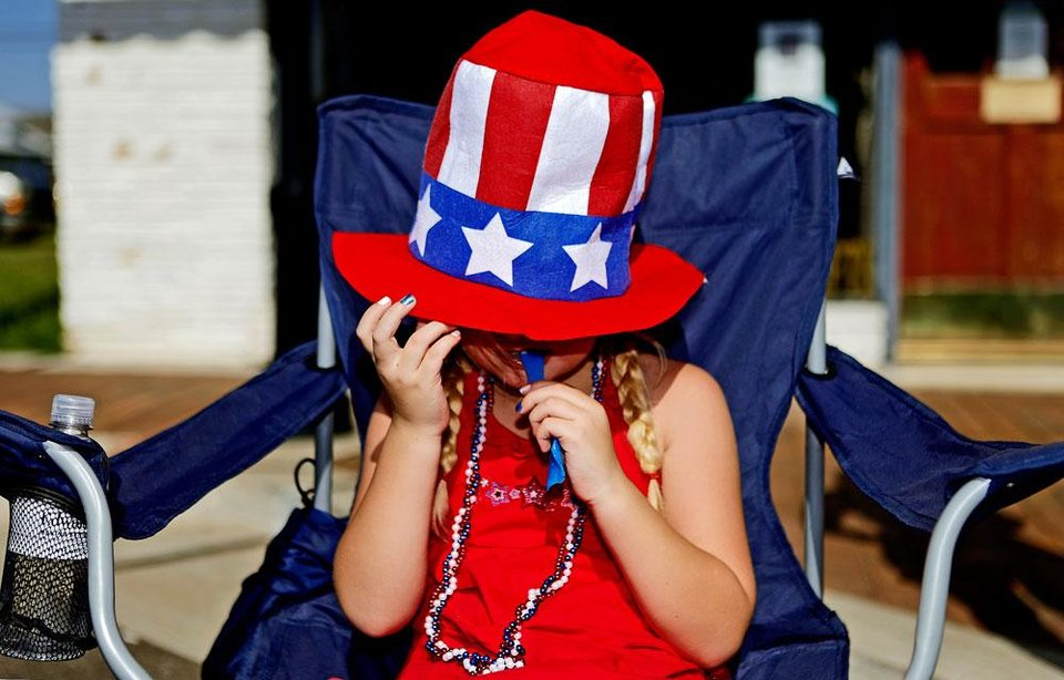 Photo -  Hannah Hargis, 6, of Edmond enjoys a snack as she watches the LibertyFest Fourth of July Parade in Edmond, Okla., Wednesday, July 4, 2012. Photo by Bryan Terry, The Oklahoman