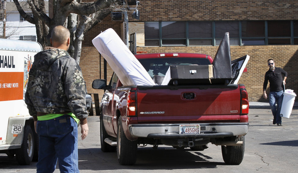 Photo - A security guard, left, directs the driver of this truck, loaded with furniture, as it backs out of the parking lot of the SAE house.  Parents, friends and fellow students helped members of the SAE  fraternity remove all furniture and personal belongings from the house Tuesday afternoon, March 10, 2015. University officials closed the house and ordered it to be vacated by Tuesday night after a video showing students affiliated with the fraternity uttering offensive racial slurs during a weekend outing.      Photo by Jim Beckel, The Oklahoman