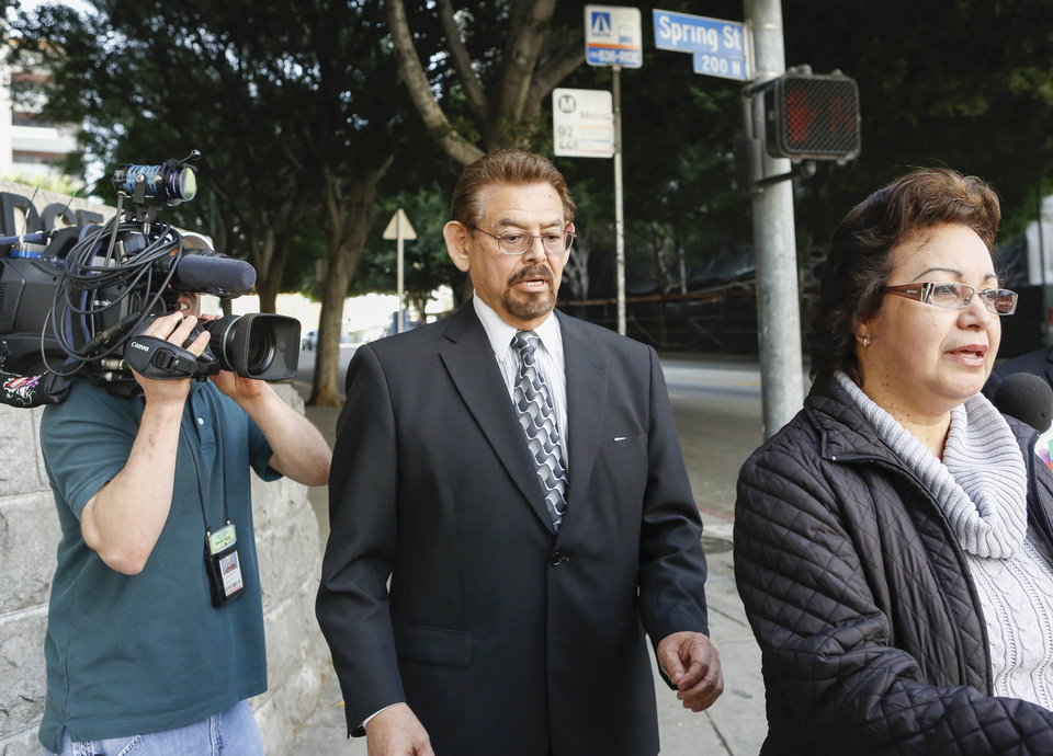 Photo - George Mirabal, a former Bell City elected official, middle, walks with unidentified members of his family,after a guilty verdict was read in his trial on Wednesday, March 20, 2013, in Los Angeles. Mirabal and four former elected officials were convicted of multiple counts of misappropriation of public funds, and a sixth defendant was cleared entirely. Former Mayor Oscar Hernandez and co-defendants Mirabal, George Cole, Teresa Jacobo, and Victor Belo were all convicted of multiple counts and acquitted of others. The charges against them involved paying themselves inflated salaries of up to $100,000 a year in the city of 36,000 people, where one in four residents live below the poverty line. (AP Photo/Damian Dovarganes)