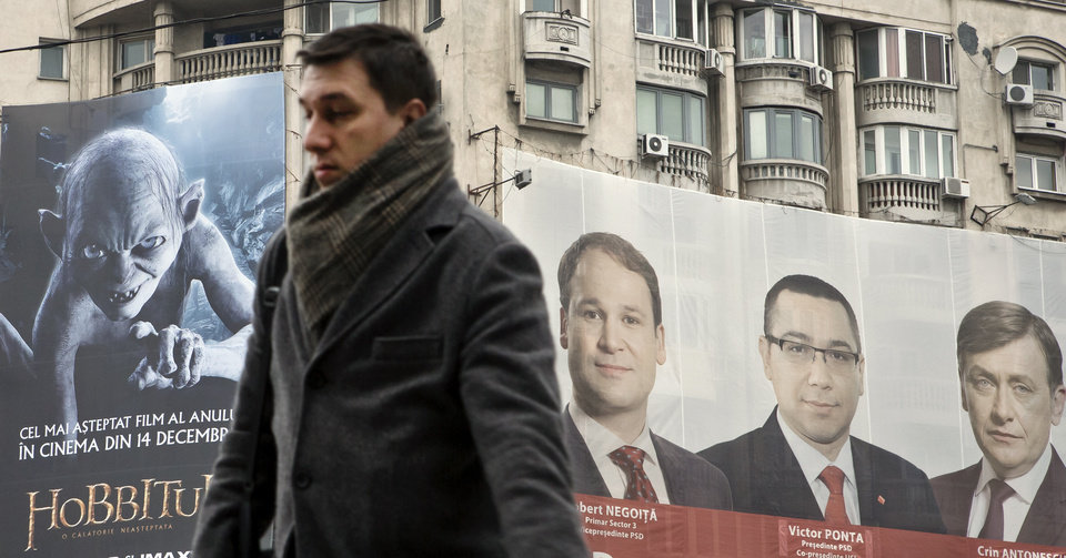CORRECTS DATE TO DEC. 5  A man walks past, backdropped by a large electoral poster for the ruling Social Liberal Union, right, and a movie poster at left,  in Bucharest, Romania, Wednesday, Dec. 5, 2012. Romania will hold parliamentary elections on Dec. 9, 2012. (AP Photo/Vadim Ghirda)