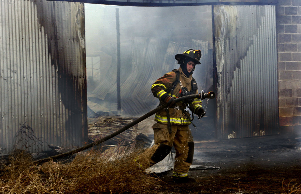 Photo - A Norman firefighter drags a hose to extinguish a fire in a barn Thursday morning on 36th Avenue SE near Post Oak Road. PHOTO BY STEVE SISNEY, THE OKLAHOMAN  STEVE SISNEY
