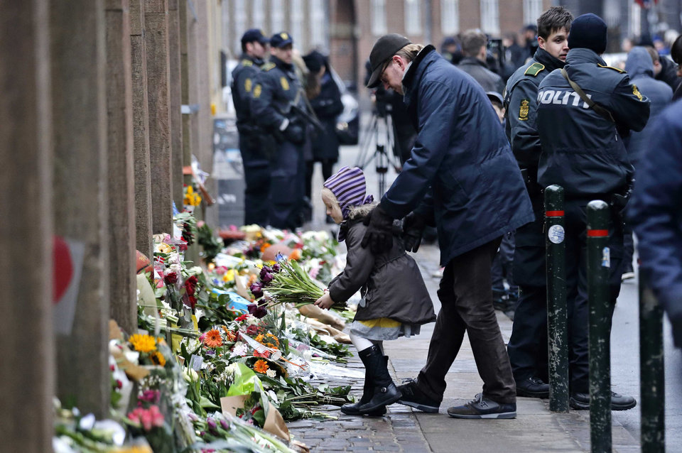 Photo - People laying flowers outside a synagogue where an attack took place, in Copenhagen, Sunday, Feb. 15, 2015. Danish police shot and killed a man early Sunday suspected of carrying out shooting attacks at a free speech event and then at a Copenhagen synagogue, killing a Danish documentary filmmaker and a member of the Scandinavian country's Jewish community. Five police officers were also wounded in the attacks. (AP Photo/Polfoto, Jens Dresling)  DENMARK OUT