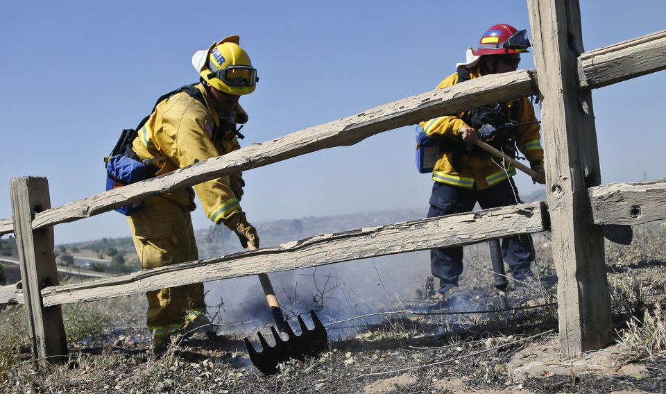 Photo - Firefighters knock out a flare up where a brush fire roared through a section of San Diego's north county, Wednesday, May 14, 2014, in San Diego.  Weather conditions that at least temporarily calmed allowed firefighters to gain ground early Wednesday on a pair of wildfires that forced thousands of residents to leave their homes. (AP Photo)
