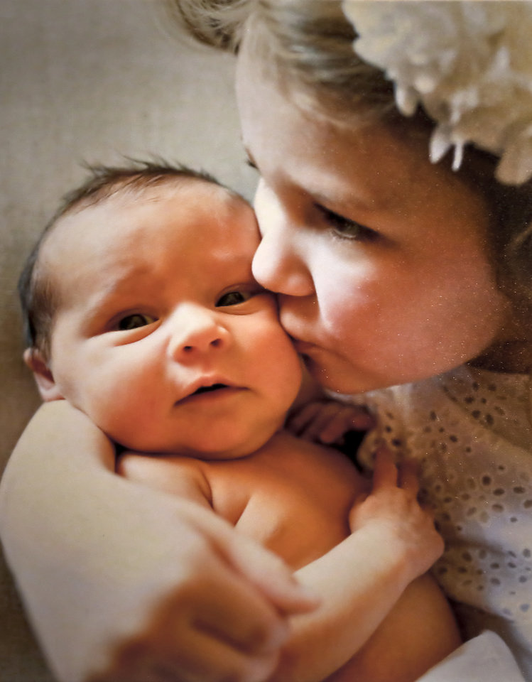 Photo -   Sophia Endicott, 4, kisses her sister Julia, 10 months. Kyle and Becky Endicott conceived Julia through in vitro fertilization after experiencing fertility problems. PHOTO PROVIDED    CHRIS LANDSBERGER -  CHRIS LANDSBERGER