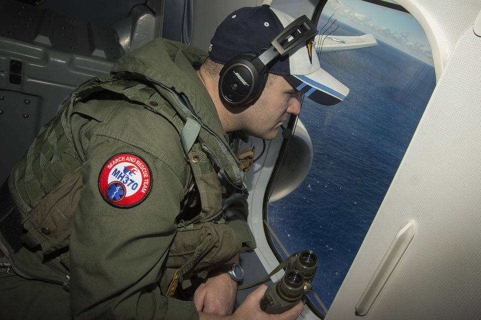 Photo - In this photo taken on Thursday, April 10, 2014, and released by the U.S. Navy, Airman 2nd Class Karl Shinn keeps watch out a window while flying in a P-8A Poseidon aircraft during a search mission looking for missing Malaysia Airlines flight MH370 over the southern Indian Ocean. (AP Photo/U.S. Navy, Chief Spc. Keith DeVinney)