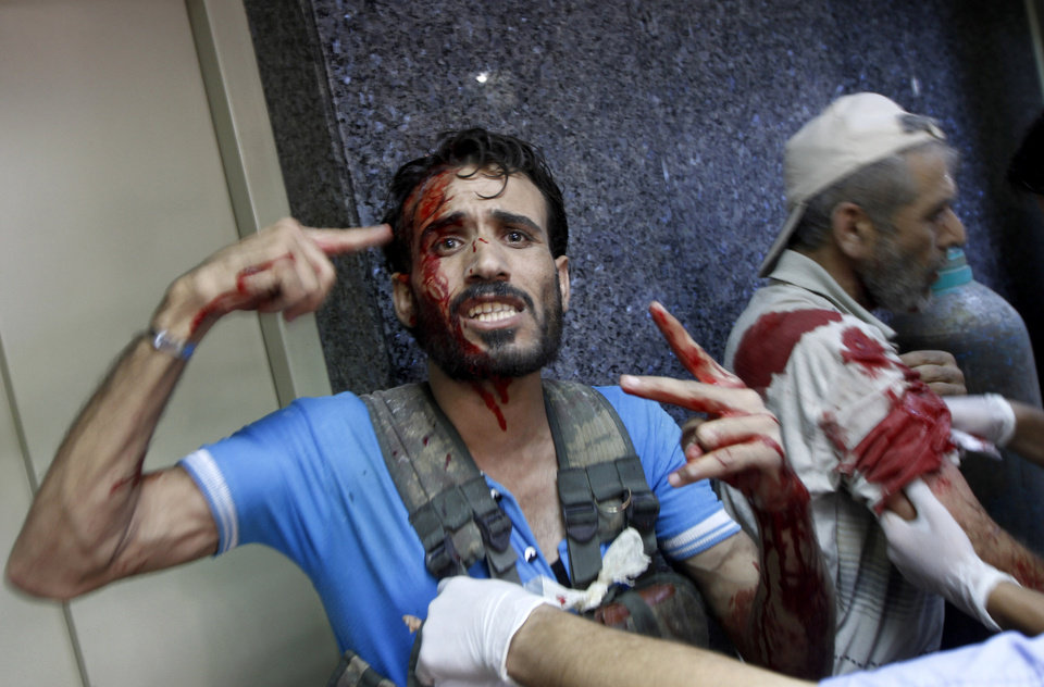 Photo -   An Syrian injured fighter arrives at a field hospital in Aleppo, Syria, Friday, Aug. 17, 2012. Rebel footholds in Aleppo have been the target of weeks of Syrian shelling and air attacks as part of wider offensives by President Bashar Assad's regime. Rebels have been driven from some areas, but the report of clashes near the airport suggests the battles could be shifting to new fronts. (AP Photo/Khalil Hamra)