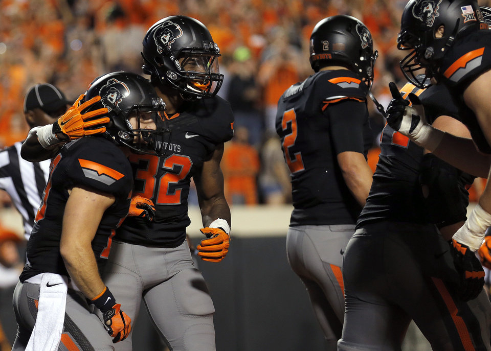 Photo - Oklahoma State's David Glidden (13) and Chris Carson (32) celebrate a Glidden touchdown in the third quarter during the college football game between the Oklahoma State Cowboys (OSU) and the Central Arkansas Bears at Boone Pickens Stadium in Stillwater, Okla., Saturday, Sept. 12, 2015. Photo by Sarah Phipps, The Oklahoman