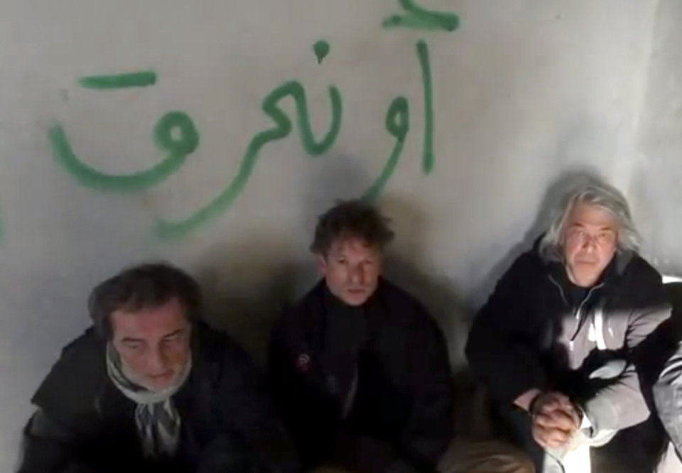 Photo - This image taken from undated amateur video posted on the Internet shows NBC chief foreign correspondent Richard Engel, center, with NBC Turkey reporter Aziz Akyavas, left, and NBC photographer John Kooistra, right, after they were taken hostage in Syria. More than a dozen heavily armed gunmen kidnapped and held Engel and several colleagues for five days inside Syria, keeping them blindfolded and tied up before they finally escaped unharmed during a firefight between their captors and anti-regime rebels, Engel said Tuesday, Dec. 18, 2012. The Arabic writing on the wall reads,