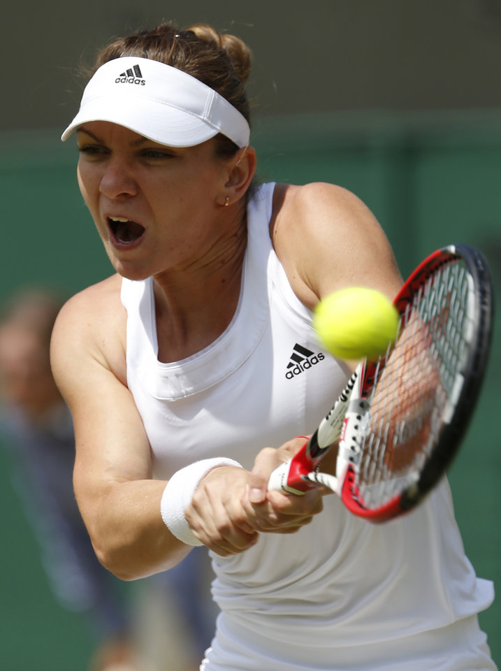 Photo - Simona Halep of Romania plays a return to Zarina Diyas of Kazakhstan during their women's singles match at the All England Lawn Tennis Championships in Wimbledon, London, Tuesday, July 1, 2014. (AP Photo/Alastair Grant)