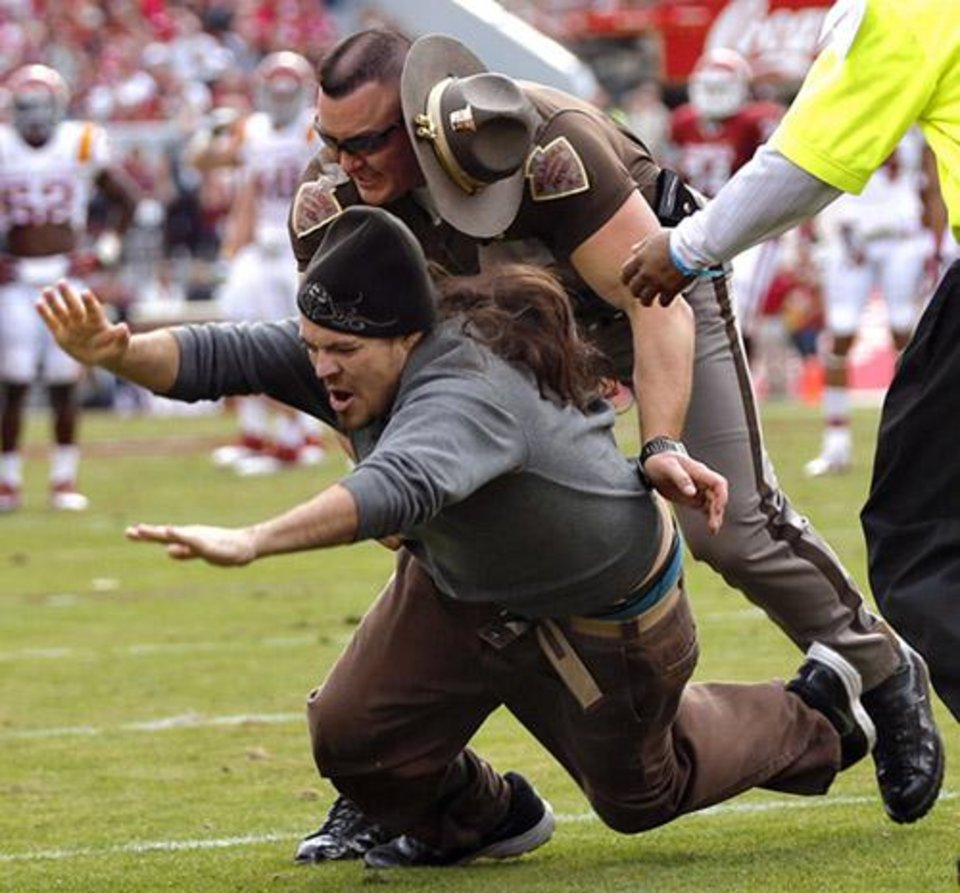 Photo -  An Oklahoma Highway Patrol officer tackles a fan that ran on the field during the college football game between the University of Oklahoma Sooners (OU) and the Iowa State University Cyclones (ISU) at Gaylord Family-Oklahoma Memorial Stadium in Norman, Okla. on Saturday, Nov. 16, 2013. Photo by Chris Landsberger, The Oklahoman