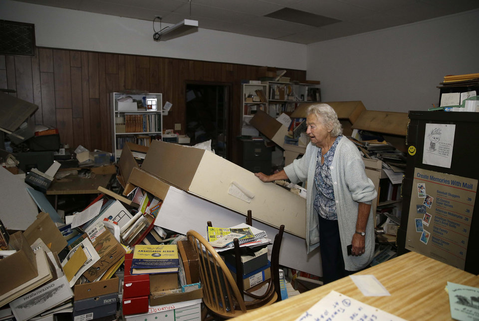 Photo - Jean Meehan looks over the damage to her JHM Stamp and Collectibles store following an earthquake Sunday, Aug. 24, 2014, in Napa, Calif. A large earthquake caused significant damage in California's northern Bay Area early Sunday, sending at least 70 people to a hospital, igniting fires, knocking out power to tens of thousands and sending residents running out of their homes in the darkness. (AP Photo/Eric Risberg)