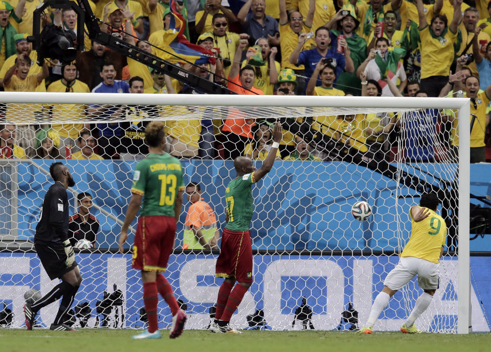 Photo - Spectators cheer as Brazil's Fred (9) scores his side's third goal against Cameroon's goalkeeper Charles Itandje during the group A World Cup soccer match between Cameroon and Brazil at the Estadio Nacional in Brasilia, Brazil, Monday, June 23, 2014. (AP Photo/Bernat Armangue)