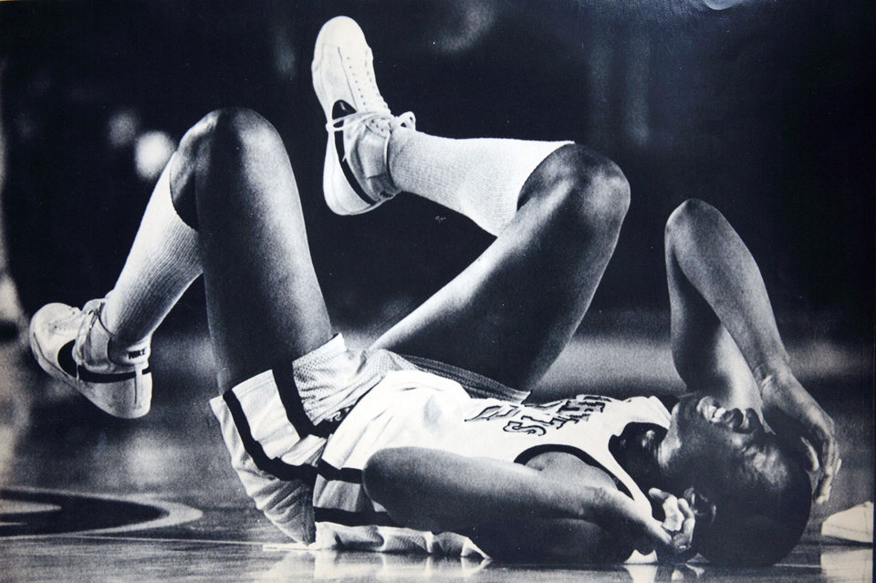 Photo - Former OU basketball player Wayman Tisdale. The second-quarter tip proves unfortunate for Tulsa Washington as its star performer. Wayman Tisdale, grimacing in pain, suffers an ankle injury against Edmond Thursday night. Staff photo by Doug Hoke. Photo taken, Photo published 3/19/1982 in The Daily Oklahoman. ORG XMIT: KOD