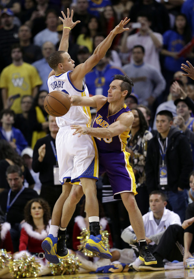 Los Angeles Lakers' Steve Nash (10) passes next to Golden State Warriors' Stephen Curry (30) during the second half of an NBA basketball game in Oakland, Calif., Saturday, Dec. 22, 2012. Los Angeles won in overtime 118-115. (AP Photo/Marcio Jose Sanchez)