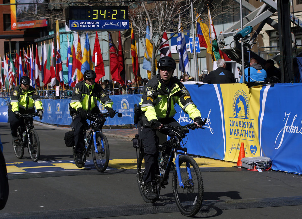 Photo - Boston Police officers on bicycles ride across the finish line before during 118th Boston Marathon Monday, April 21, 2014 in Boston. (AP Photo/Elise Amendola)