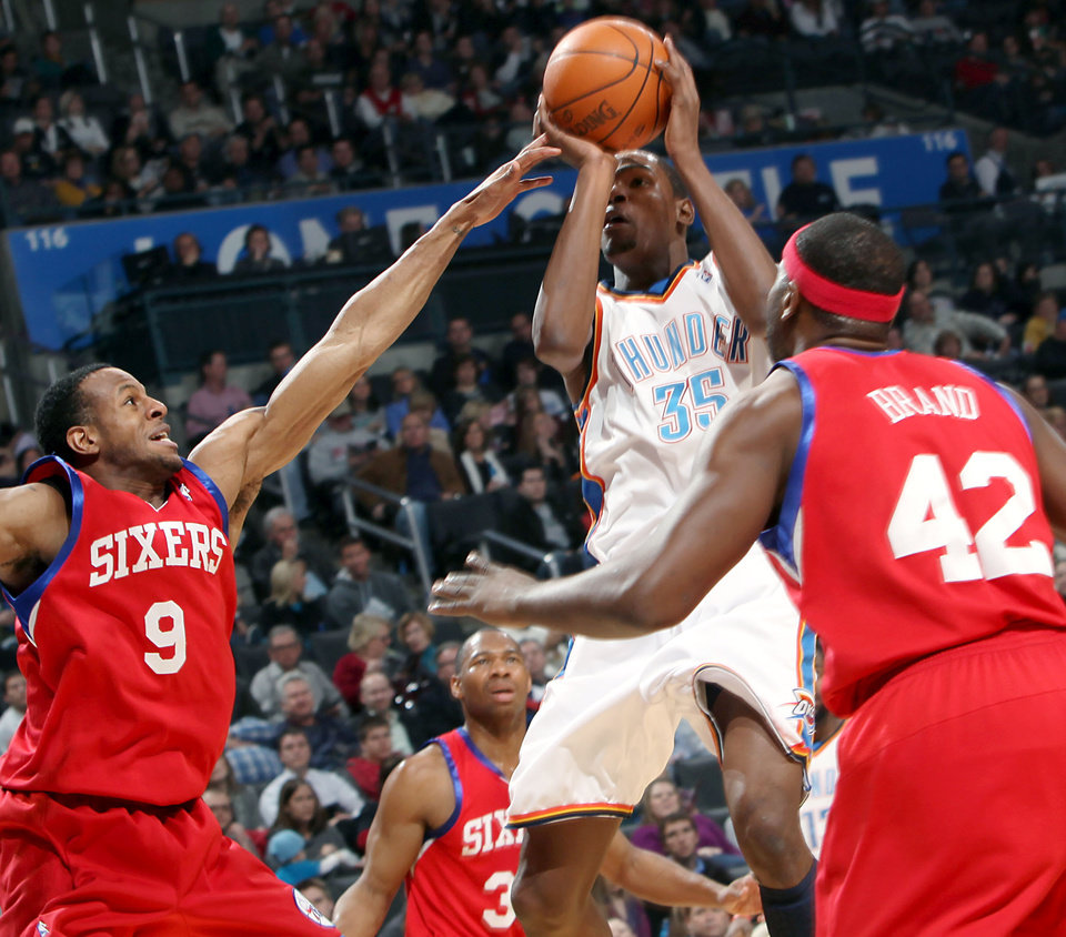 Photo - Oklahoma City's Kevin Durant puts up a shot in front of Philadelphia's Andre Iguodala (#9) Willie Green (#33) and Elton Brand (#42) during the first half of their NBA basketball game at the Ford Center in Oklahoma City on Tuesday, Dec. 2, 2009. By John Clanton, The Oklahoman