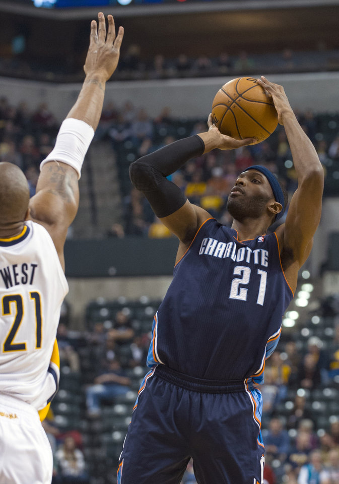 Photo - Charlotte Bobcats' Hakim Warrick (21) shoots against Indiana Pacers' David West (21) during the first half of an NBA basketball game in Indianapolis, Saturday, Jan. 12, 2013. (AP Photo/Doug McSchooler)