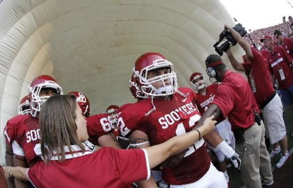 Photo - Oklahoma's Tom Wort (12) wears Austin Box's jersey as he leads the Sooners onto the field during the college football game between the University of Oklahoma Sooners ( OU) and the Tulsa University Hurricanes (TU) at the Gaylord Family-Memorial Stadium on Saturday, Sept. 3, 2011, in Norman, Okla. Photo by Chris Landsberger, The Oklahoman ORG XMIT: KOD