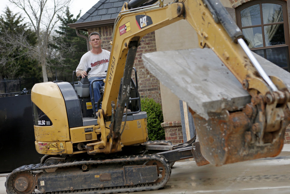 Photo - Robert Ozment, with Smart Shelters Inc., operates a track hoe as he installs a storm shelter at Patrick and Kim Lenow's Oklahoma City home. Photo by BRYAN TERRY, THE OKLAHOMAN