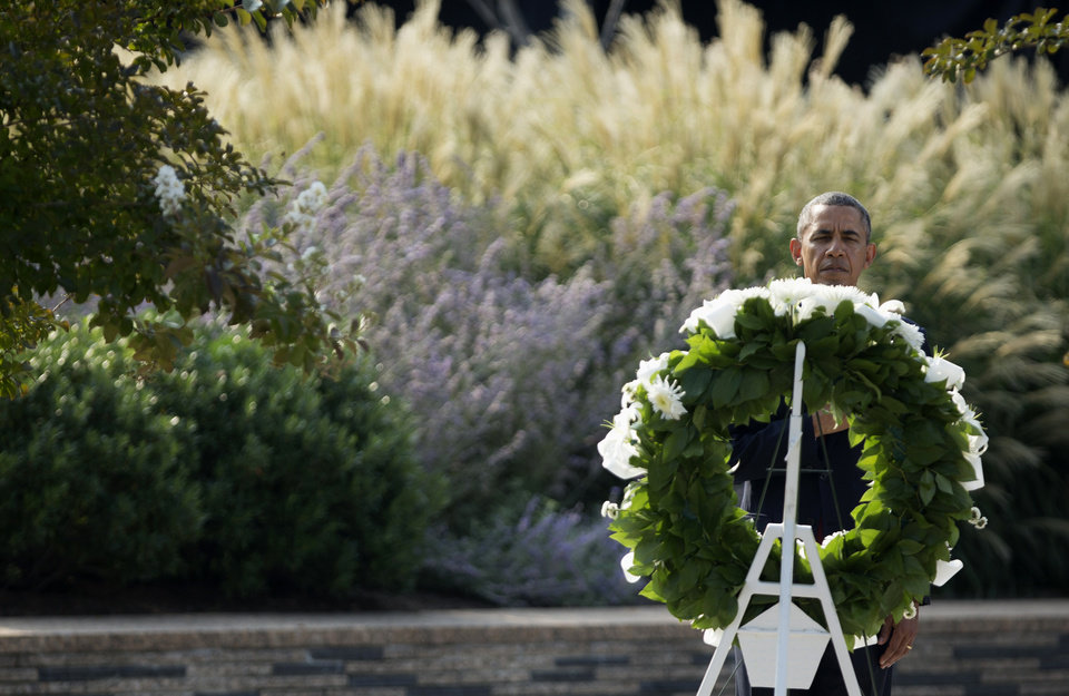 Photo - President Barack Obama lays a wreath at the Pentagon, Wednesday, Sept. 11, 2013, during a ceremony marking the 12th anniversary of the worst terror attack on the US. The Pentagon was struck by one of the hijacked plane.  (AP Photo/Manuel Balce Ceneta)