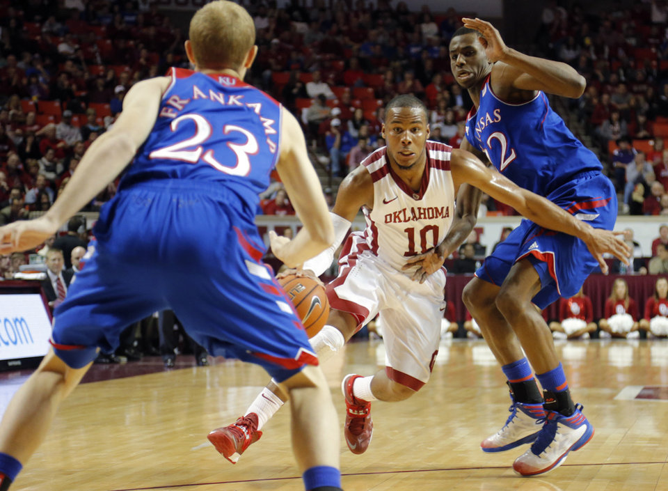 Photo - Oklahoma's Jordan Woodard (10) drives against Kansas' Conner Frankamp (23) and Andrew Wiggins (22) during the NCAA college basketball game between the University of Oklahoma Sooners (OU) and the University of Kansas (KU) Jayhawks at Lloyd Nobel Center in Norman,  Okla. on Wednesday, Jan. 8, 2014.   .Photo by Chris Landsberger, The Oklahoman