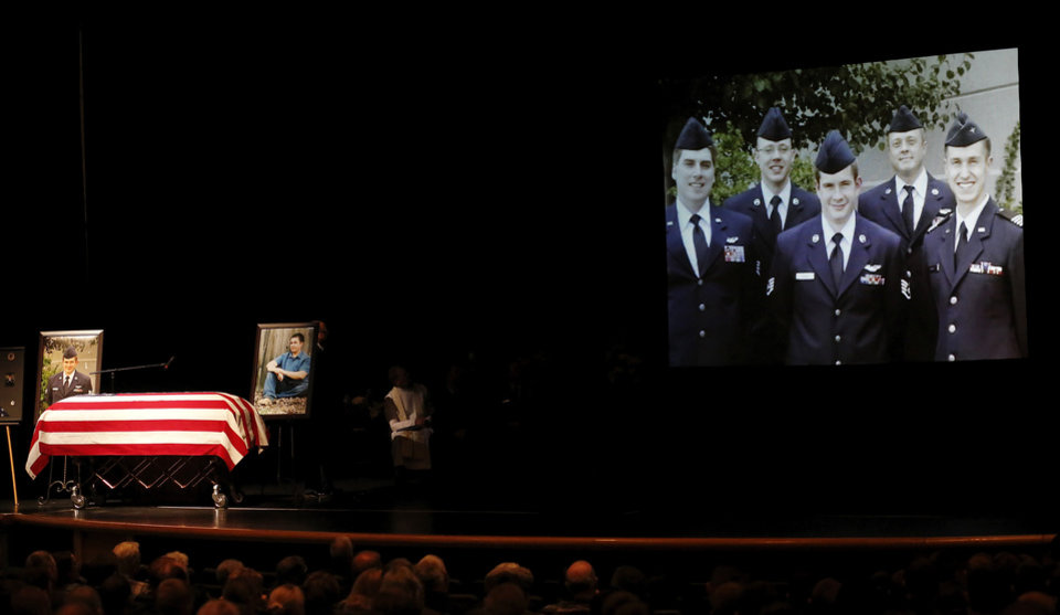 Photo - A video tribute to SSgt. Daniel Fannin is shown during the service on a large screen above his flag-draped casket More than 1,700 people, many of whom were dressed in the US Air Force's  dark blue service dress uniform, filled the lower and upper levels of the Rose State College Performing Arts Center Monday morning, May, 13, 2013, to attend a memorial service for SSgt. Daniel N. Fannin, a brother in arms killed April 27 in a palne crash while on a mission in Afghanistan.  Fannin , 30, was assigned to the 552nd Operations Support Squadron at Tinker Air Force base. He joined the Air Force in 2001. Photo  by Jim Beckel, The Oklahoman.