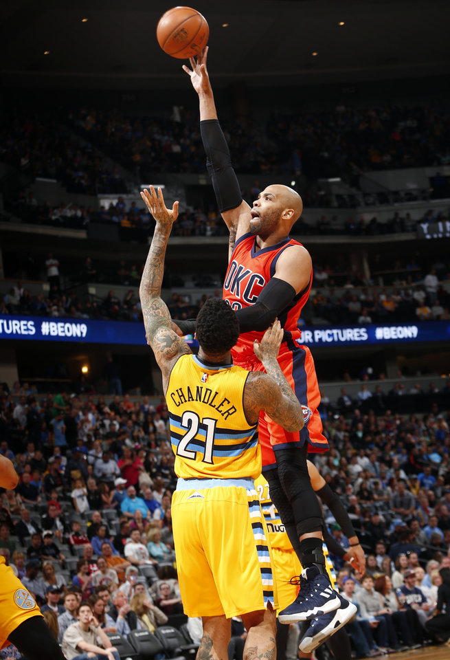 Photo - Oklahoma City Thunder forward Taj Gibson (22) goes up for a shot against Denver Nuggets forward Wilson Chandler (21) during the first half of a basketball game Sunday, April 9, 2017, in Denver. (AP Photo/Jack Dempsey)