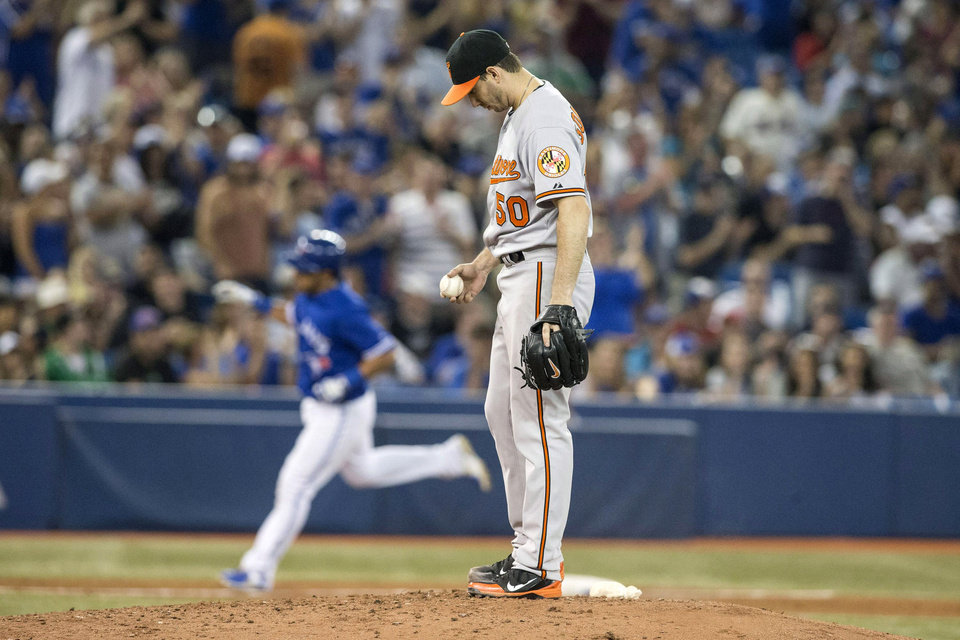 Photo - Baltimore Orioles pitcher Miguel Gonzalez reacts on the mound as Toronto Blue Jays' Maicer Izturis rounds the bases after hitting a home run during the fifth inning of a baseball game in Toronto, Saturday June 22, 2013. (AP Photo/the Canadian Press, Chris Young)