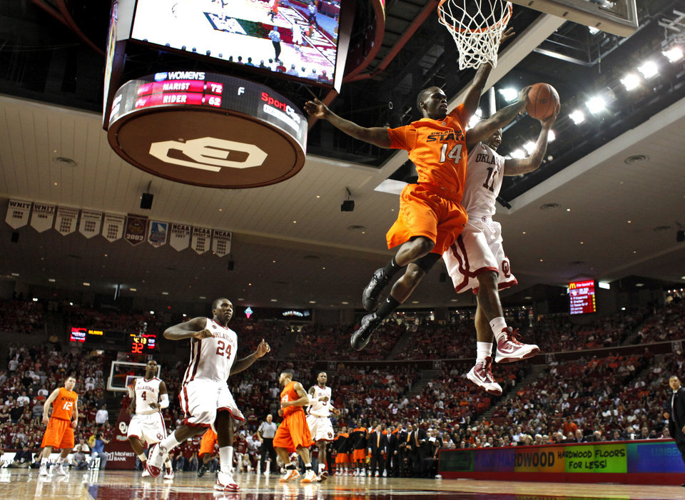 Photo - OU's Tommy Mason-Griffin (11) fights for a shot with OSU's Ray Penn (14) during the first half of the college bedlam basketball game between The University of Oklahoma Sooners (OU) and Oklahoma State University University Cowboys (OSU) at the Lloyd Noble Center on Monday, Jan. 11, 2010, in Norman, Okla.