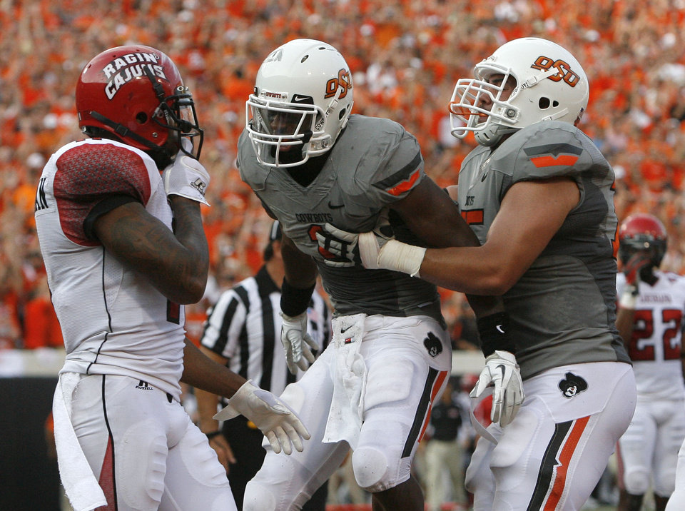 Oklahoma State\'s Joseph Randle and Nick Martinez celebrate a touchdown in front of a Louisiana-Lafayette\'s player on Saturday. Photo by Sarah Phipps, The Oklahoman