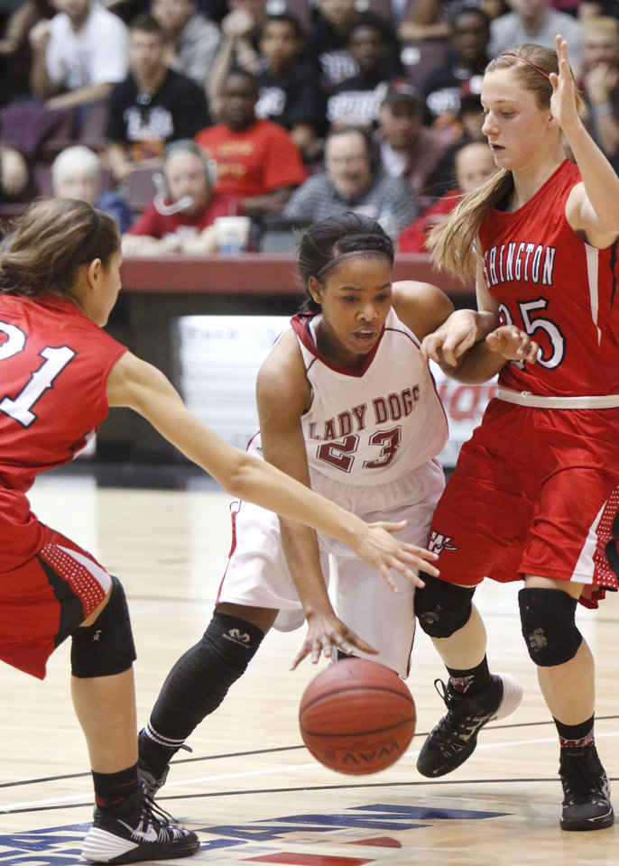Photo - Spiro's Kanisha Hutchinson drives through Washington defenders #21 Nevada Denton and #25 Brenna Busby during the Class 3A Girls quarterfinal basketball game at Southern Nazarene University's Sawyer Center in Bethany, OK, Thursday, March 13, 2014,  Photo by Paul Hellstern, The Oklahoman