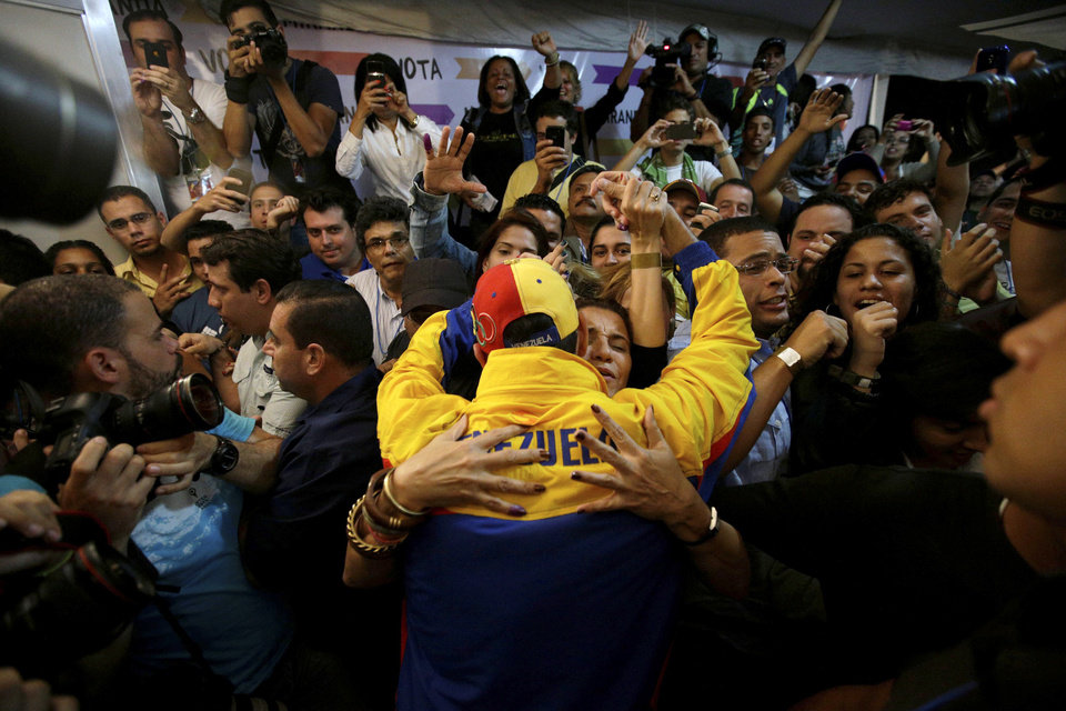 Photo - Miranda State's Gov. Henrique Capriles, center, is congratulated by his his supporters after being re-elected during an elections in Caracas, Venezuela, Sunday, Dec. 16, 2012. Capriles lost to Chavez in the country's October election, and his re-election Sunday will allow him to cement his position as Venezuela's dominant opposition leader, even as other opposition candidates floundered.(AP Photo/Fernando Llano)