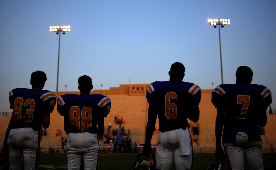 Photo - Northwest Classen players stand during the national anthem before a high school football game at Taft Stadium in Oklahoma City, Thursday, September 20, 2012. Photo by Bryan Terry, The Oklahoman