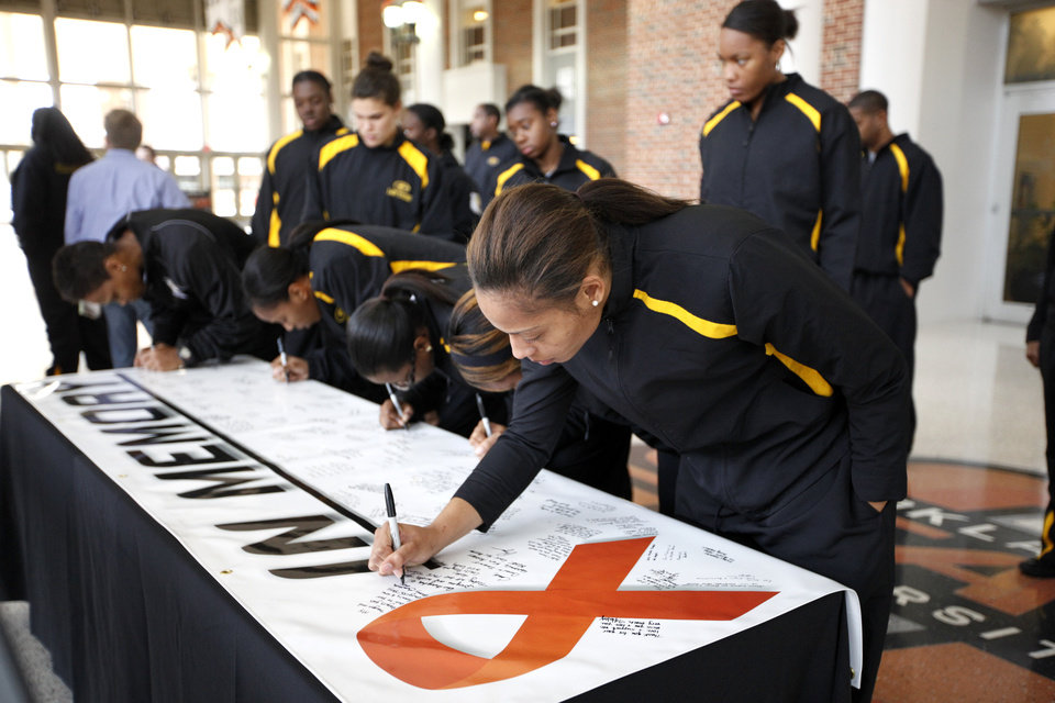 Grambling women's basketball player Tonishea Mack signs a memorial banner for OSU women's head coach Kurt Budke and assistant coach Miranda Serna at Gallagher-Iba Arena in Stillwater, Okla.,  Friday, Nov. 18, 2011.  Photo by Sarah Phipps, The Oklahoman