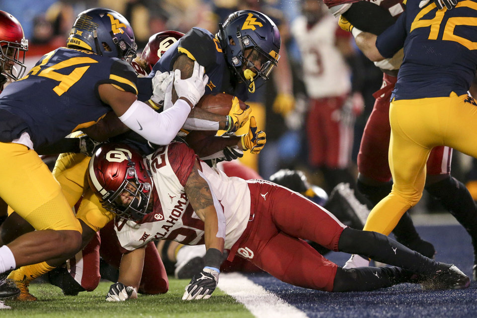 Photo - West Virginia Mountaineers running back Kennedy McKoy (6) lunges over Oklahoma Sooners safety Robert Barnes (20) while scoring a touchdown during the NCAA football game between the Oklahoma Sooners and the West Virginia Mountaineers at Mountaineer Field at Milan Puskar Stadium in Morgantown, W.Va on Friday, November 23, 2018. IAN MAULE/Tulsa World