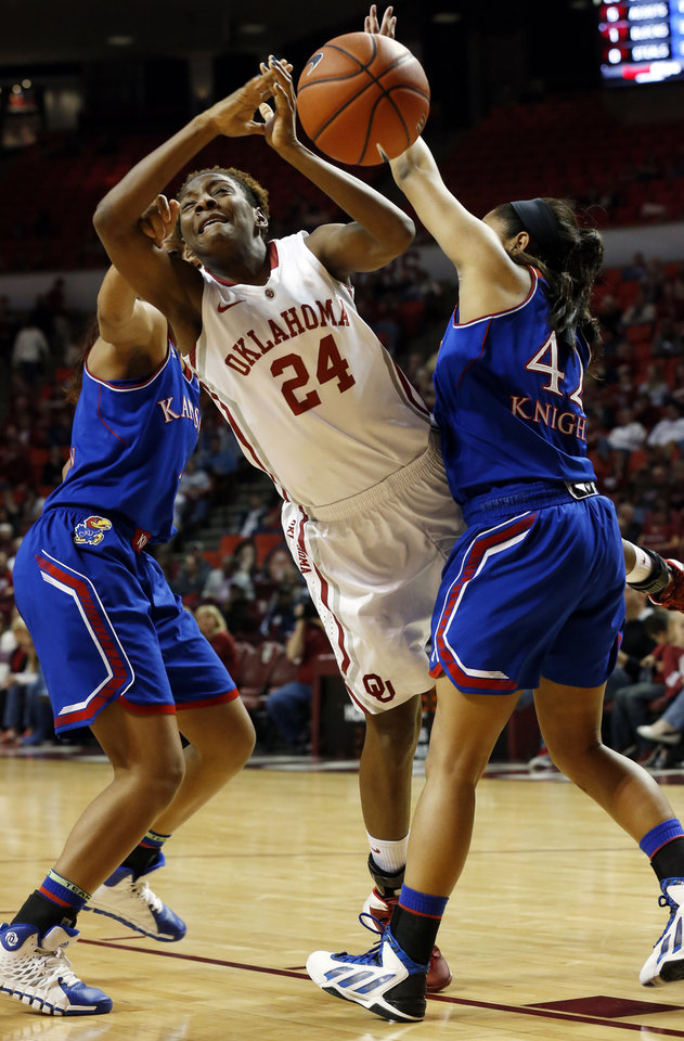 Photo - Sharane Campbell (24) is folded on a drive to the basket by Kansas Jayhawk's Jada Brown (back) as she as the University of Oklahoma Sooners (OU) play the Kansas Jayhawks in NCAA, women's college basketball at The Lloyd Noble Center on Saturday, Feb. 22, 2014  in Norman, Okla. Photo by Steve Sisney, The Oklahoman