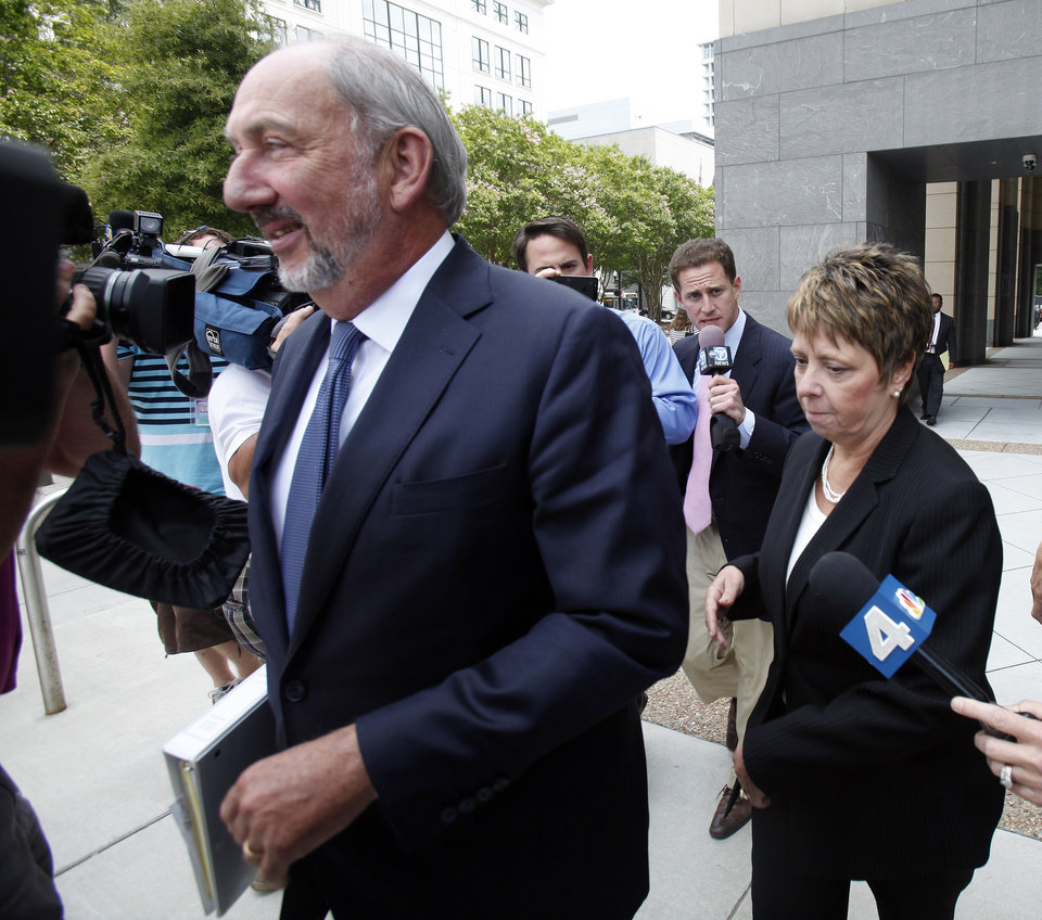 Photo - Jerri Fulkerson, right, Jonnie Williams's assistant, follows a path cleared by her attorney George Terwilliger as she left federal court after completing her testimony in the corruption trial of former Virginia Gov. Bob McDonnell and his wife Maureen, Wednesday, July 30, 2014 in Richmond, Va. (AP Photo/Richmond Times-Dispatch, James H. Wallace)