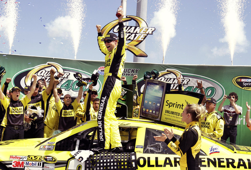 Photo - Matt Kenseth celebrates with his crew members in the winner's circle after capturing the NASCAR Sprint Cup auto race at Kentucky Speedway in Sparta, Ky., Sunday, June 30, 2013. (AP Photo/Garry Jones)