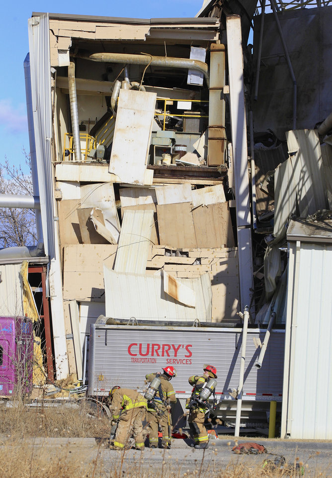Photo - Firefighter stage outside the International Nutrition plant in Omaha, Neb., Monday, where a fire and explosion took place Jan. 20, 2014. At least nine people have been hospitalized and others could be trapped at the animal feed processing plant. (AP Photo/Nati Harnik)