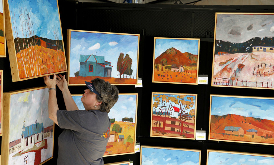 Photo -  Laurie Dale Keffer tags paintings done by her husband, Oklahoma City artist Jim Keffer, in preparation for the 2012 Festival of the Arts. Photo by Doug Hoke, The Oklahoman  DOUG HOKE